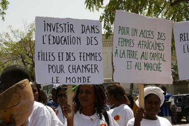 "Posters read: (l) ""Invest in education of girls and women to change the world"" and (r) ""For access of African women to land, capital and markets"". Image by Flickr user CNCD-11.11.11 (CC BY-NC-SA 2.0)."