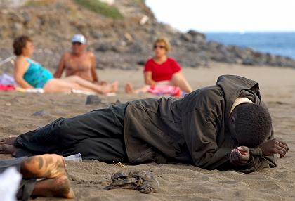An exhausted would-be immigrant rests beside sunbathing tourists on the beach near Tuineje, on Fuerteventura Island in the Spanish Canary Islands, via Noborder on Flickr CC-BY-20