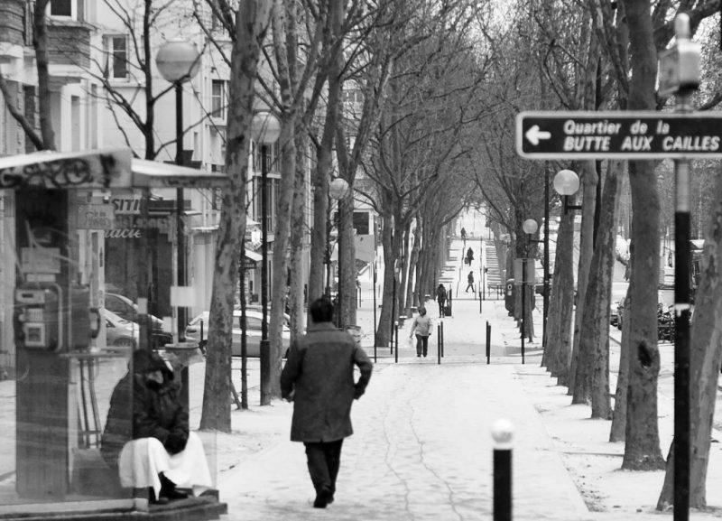 """Un homme passe devant un SDF abrité dans une cabine téléphonique, dans une rue parisienne enneigée. Photo de Gustave Deghilage publiée sur Flickr sous licence <a href=""""https://creativecommons.org/licenses/by-nc-nd/2.0/"""">CC BY-NC-ND 2.0</a>."""