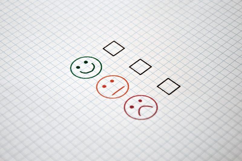 Feuille à carreaux avec 3 options à cocher, sous forme d'emojis : content, neutre, mécontent.