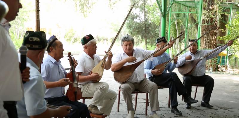 Un groupe d'hommes ouïghours assez âgés jouent de divers instruments lors d'un mechrep.